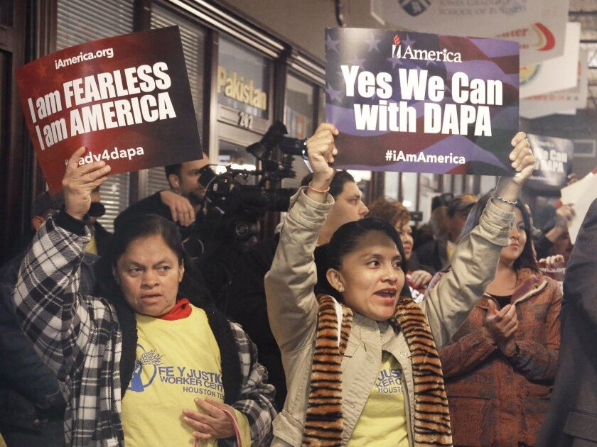 People cheer and hold up signs during a Feb. 17 town hall forum in Houston to help immigrants learn and prepare for programs under President Obama's immigration order.