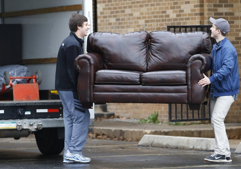 Two men load a couch from the now closed University of Oklahoma's Sigma Alpha Epsilon fraternity house into a moving truck, in Norman, Okla.