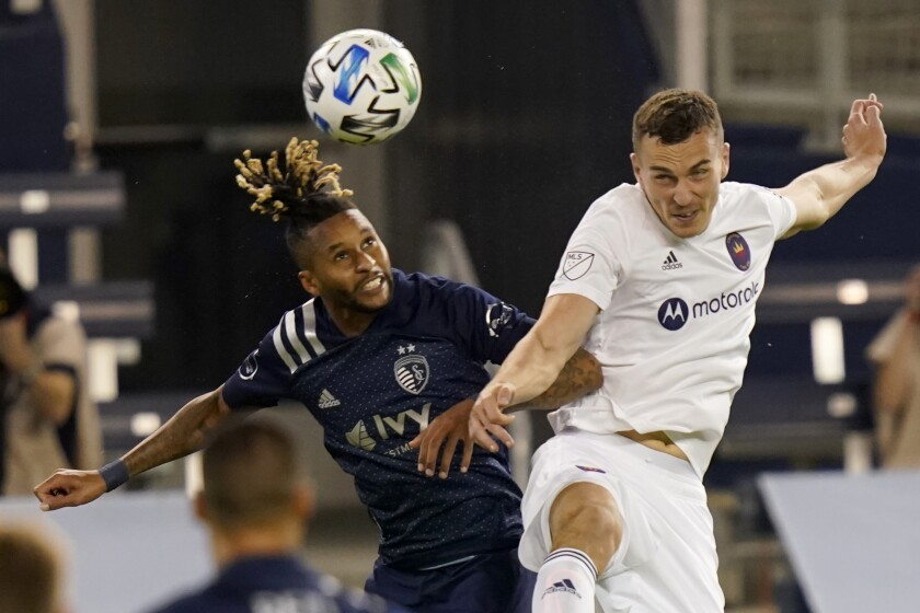 Sporting Kansas City defender Amadou Dia, left, heads the ball next to Chicago Fire defender Boris Sekulic during the first half of an MLS soccer match in Kansas City, Kan., Wednesday, Oct. 7, 2020. (AP Photo/Orlin Wagner)