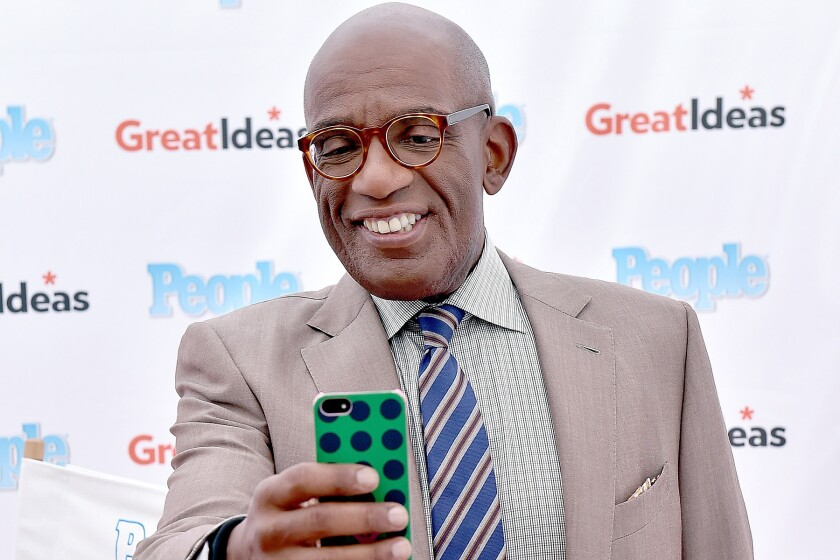 """""""Today"""" show host Al Roker holds up a cellphone at an event."""