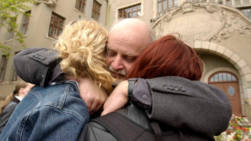 Teacher Rainer Heise hugs two students in front of the Gutenberg school in Erfurt, Germany, on April 29, 2002, three days after a 19-year-old gunman killed 16 people and then himself at the school.