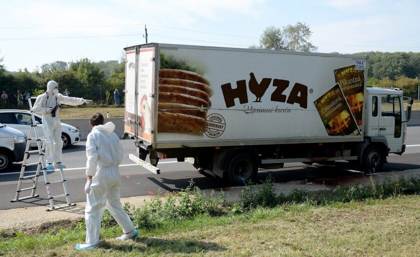 Forensic experts investigate a truck in which at least 20 migrants were found dead on an Austrian highway on Aug. 27.