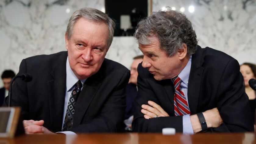 Sen. Mike Crapo (R-Idaho), left, chairman of the Senate Banking Committee, talks with Sen. Sherrod Brown (D-Ohio) before a hearing Nov. 28.