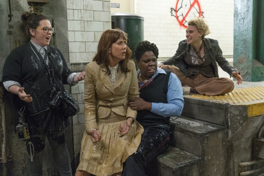 """Abby (Melissa McCarthy), left, Erin (Kristen Wiig) and Patty (Leslie Jones) get slimed as Holtzmann (Kate McKinnon) watches in the new """"Ghostbusters."""""""
