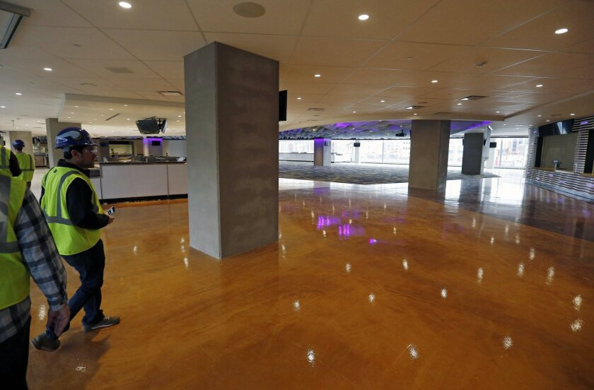 Members of the media take a tour, Tuesday, Feb. 16, 2016, of the new U.S. Bank stadium in Minneapolis which will be home to the Minnesota Vikings NFL football team. The billion-dollar stadium is 90 percent completed. (AP Photo/Jim Mone)