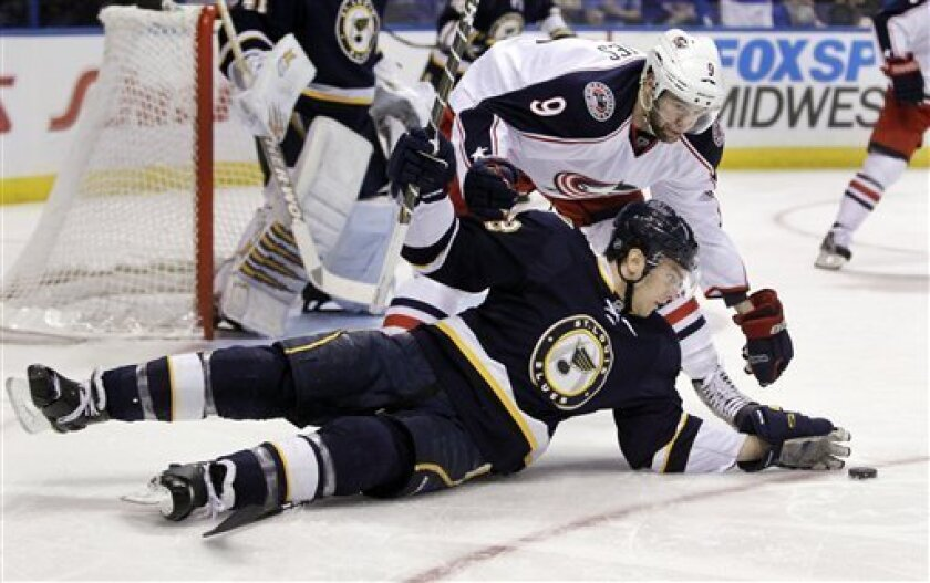 St. Louis Blues' Kevin Shattenkirk, front, reaches for a puck after being tripped up by Columbus Blue Jackets' Colton Gillies, top, during the first period of an NHL hockey game, Saturday, March 31, 2012, in St. Louis. (AP Photo/Jeff Roberson)