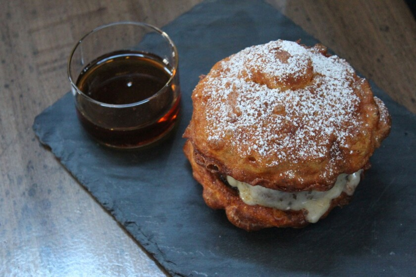 The Monte Cristo burger by Michael Voltaggio includes a signature beef patty, Gruyere fondue, prosciutto and a custard-soaked, fried bun. It comes topped with powdered sugar and a side of maple syrup.