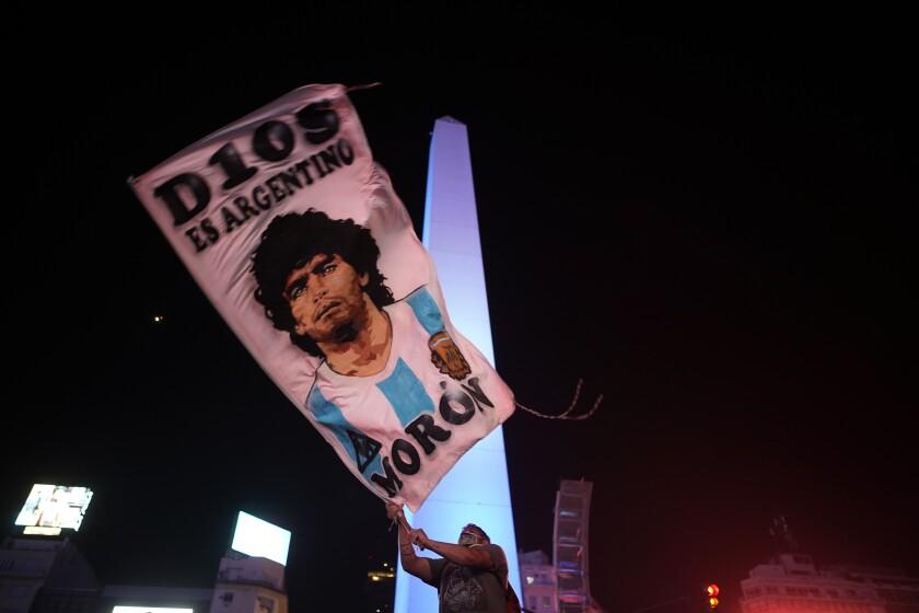 Un individuo ondea una bandera con la imagen de Diego Maradona en el centro de Buenos Aires