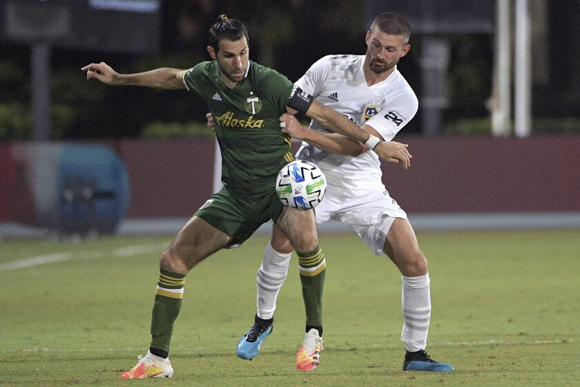 Portland Timbers midfielder Diego Valeri and Galaxy defender Perry Kitchen compete for the ball on Monday in Kissimmee, Fla.