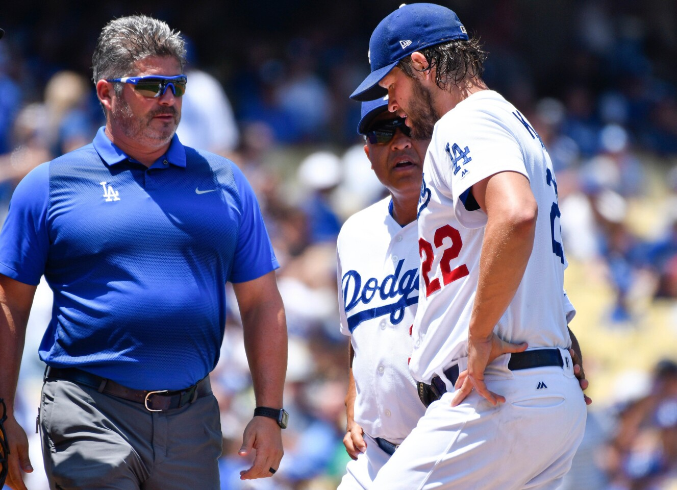 Jul 23, 2017; Los Angeles, CA, USA; Los Angeles Dodgers starting pitcher Clayton Kershaw (22) talks to manager Dave Roberts (center) and trainer Nate Lucero after injuring himself in the second inning against the Atlanta Braves at Dodger Stadium. After throwing a few warmup pitches Kershaw stayed in the game but was pulled in the next inning. Mandatory Credit: Robert Hanashiro-USA TODAY Sports ** Usable by SD ONLY **