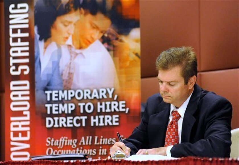 In this May 24, 2011 photo, unemployed electrical engineer William Love of Pasadena, Md., whose unemployment benefits have been exhausted, fills out an application for a sales position at a job fair in Linthicum, Md. Fewer people sought unemployment benefits last week, though applications remain stuck at high levels that signal weak job growth. (AP Photo/Steve Ruark)