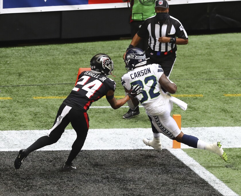 Seattle Seahawks running back Chris Carson, front right, gets into the end zone past Atlanta Falcons cornerback A.J. Terrell, left, during the first quarter of an NFL football game Sunday, Sept. 13, 2020, in Atlanta. (Curtis Compton/Atlanta Journal-Constitution via AP)