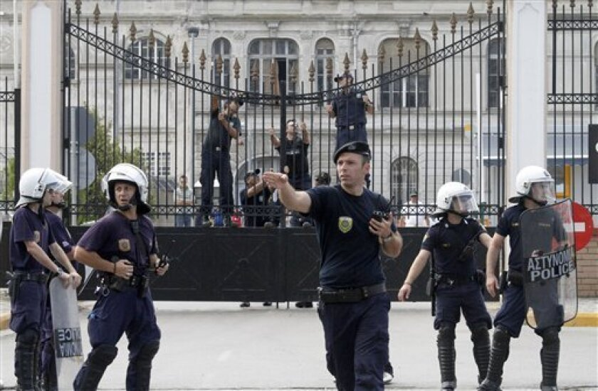 Coast guards lock the gate of the harbor as riot police take positions during a protest in Thessaloniki, Greece Friday Sept. 10, 2010. Unions are staging protests in Thessaloniki ahead of an annual weekend speech on the state of the economy by Prime Minister George Papandreou. Unions are angry at plans by Papandreou's Socialist government to sell-off and reform loss-making state enterprises and relax labor rules as part of an effort deal with Greece's acute debt crisis. (AP Photo/Dimitri Messinis)
