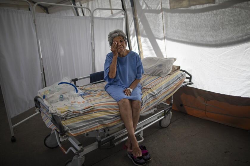 Nancy Rodriguez, de 76 años y enferma con COVID-19, se seca las lágrimas mientras habla de su batalla contra el virus en una tienda de campaña para pacientes que serán dados de alta del hospital Pérez de León II, un hospital público en el que opera la organización Médicos sin fronteras en el barrio de Petare, Caracas. (AP Foto/Ariana Cubillos)
