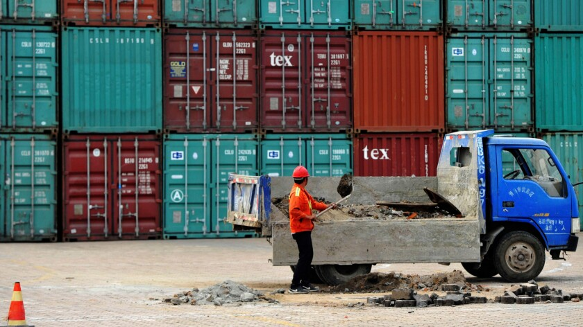 A worker repairs the ground at a container port in Qingdao in eastern China's Shandong province on June 8.