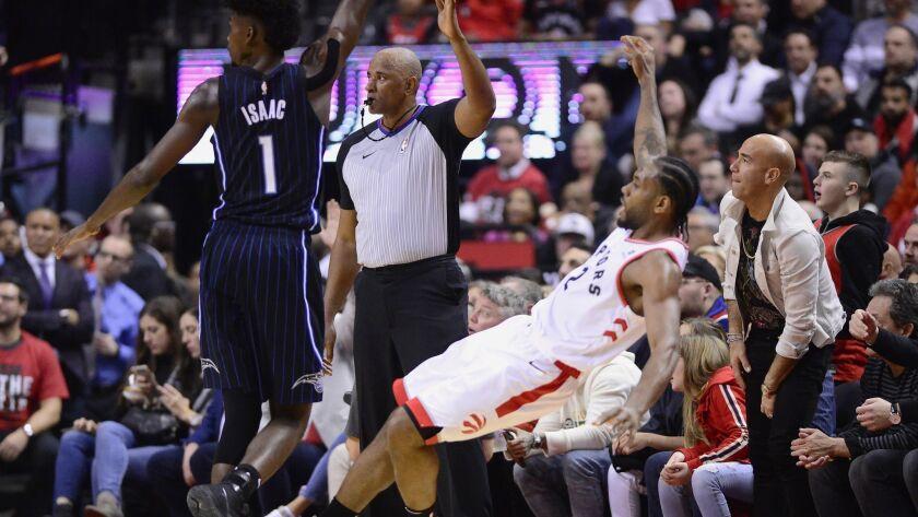 Toronto Raptors forward Kawhi Leonard (2) falls backward as he makes a 3-point basket, next to Orlan