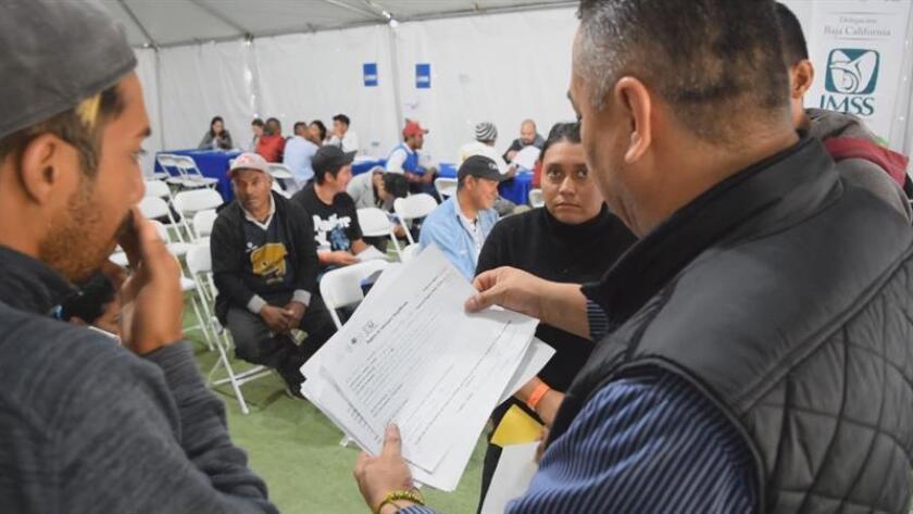 Fotograma estraído de un video fechado hoy, 21 de nociembre de 2018, que muestra a integrantes de la caravana migrante que recibien ofertas de empleo formal en la ciudad mexicana de Tijuana, frontera con Estados Unidos. MÁXIMA CALIDAD DISPONIBLE.