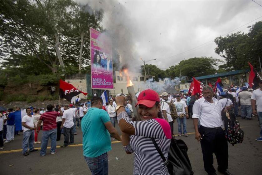 """Una mujer simpatizante del partido Frente Sandinista de Liberación Nacional (FSLN), lanza un mortero durante una caminata denominada """"Justicia para las víctimas del terrorismo"""" en Managua (Nicaragua). EFE/Archivo"""
