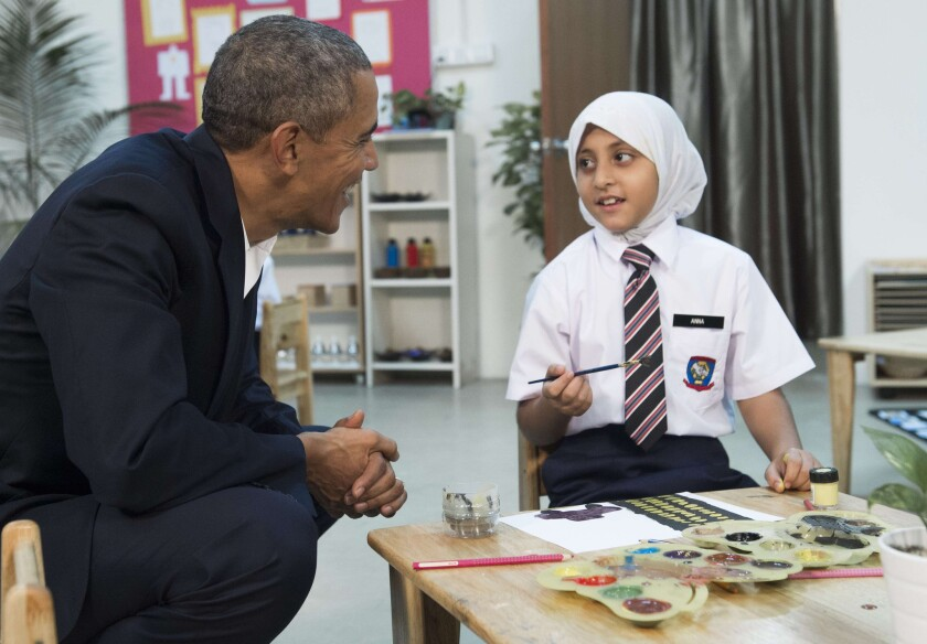 President Obama speaks with a young girl as he tours the Dignity for Children Foundation in Kuala Lumpur, Malaysia, on Saturday. The girl was rescued from traffickers after being separated from her family as they fled Myanmar and will be resettled in the United States.