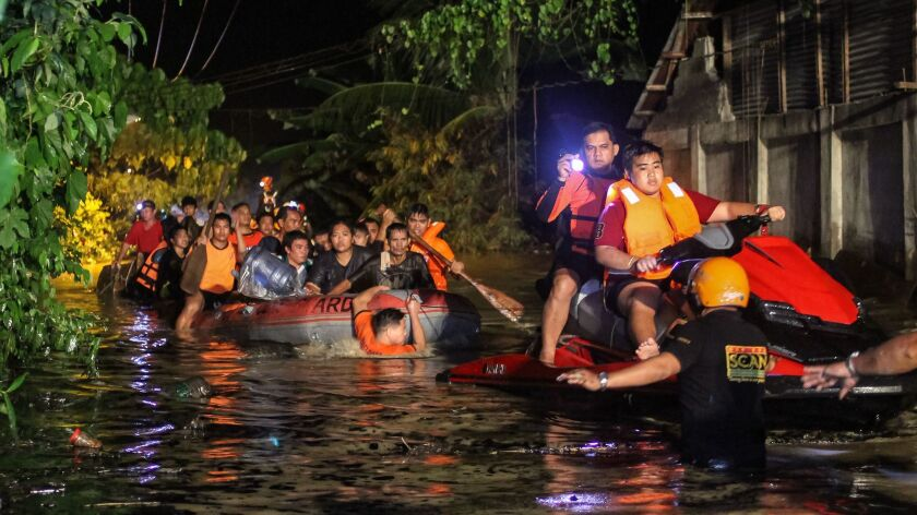 Rescue workers evacuate flood-affected residents in Davao on the southern Philippine island of Mindanao early Saturday.