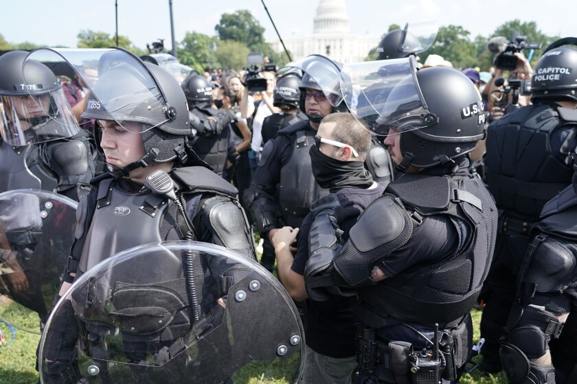 """Police circle a man, center with glasses, during a rally near the U.S. Capitol in Washington, Saturday, Sept. 18, 2021. The rally was planned by allies of former President Donald Trump and aimed at supporting the so-called """"political prisoners"""" of the Jan. 6 insurrection at the U.S. Capitol. (AP Photo/Gemunu Amarasinghe)"""