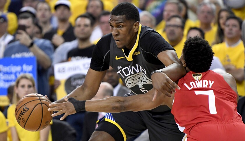 Toronto Raptors guard Kyle Lowry (7) reaches for the ball controlled by Golden State Warriors center