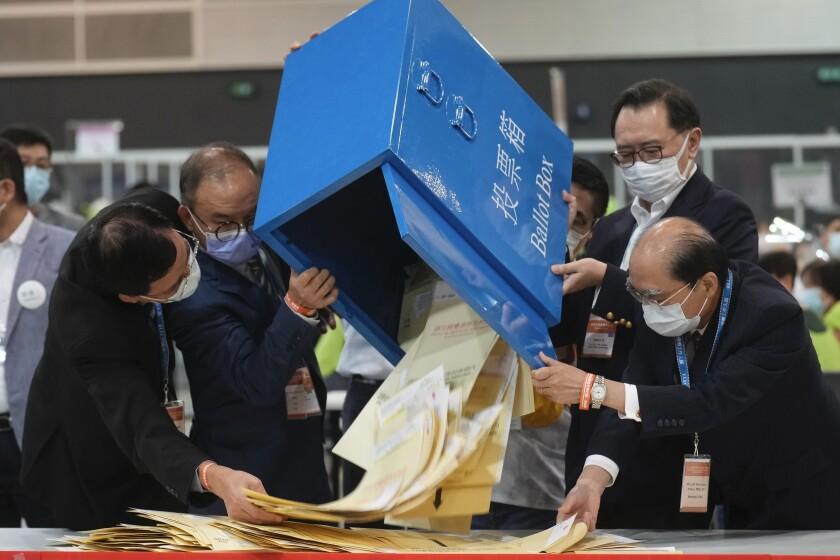 Erick Tsang, segundo por la izquierda, el secretario de la Oficina Constitucional y de Asuntos del Continente, ayuda a funcionarios a sacar la boletas de una caja en un centro de votación en Hong Kong, el domingo 19 de septiembre de 2021. (AP Foto/Vincent Yu)