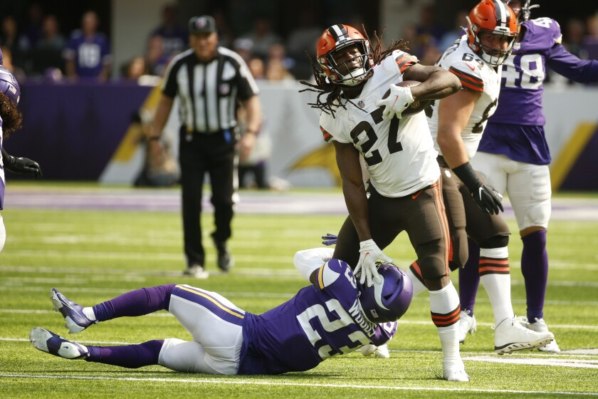 Cleveland Browns running back Kareem Hunt (27) runs from Minnesota Vikings free safety Xavier Woods (23) during the first half of an NFL football game, Sunday, Oct. 3, 2021, in Minneapolis. (AP Photo/Bruce Kluckhohn)