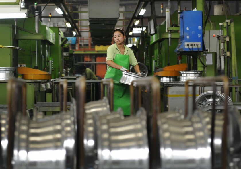 In this Thursday, Aug. 21, 2014 photo, a woman works at a factory manufacture aluminum wheel hubs in Zouping county in east China's Shandong province. Chinese premier Li Keqiang promised Wednesday, Sept. 10, 2014 to open its economy wider to foreign businesses, promising favorable conditions amid a wave of anti-monopoly investigations that business groups say might be aimed at limiting competition. (AP Photo) CHINA OUT