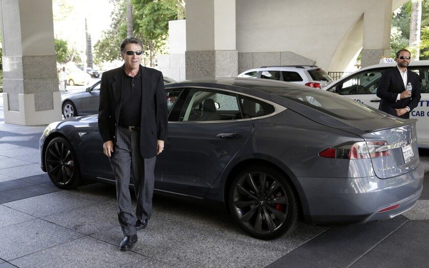 Then-Texas Gov. Rick Perry arrives in a Tesla Motors Type S electric car for a meeting with state lawmakers in Sacramento in 2014.