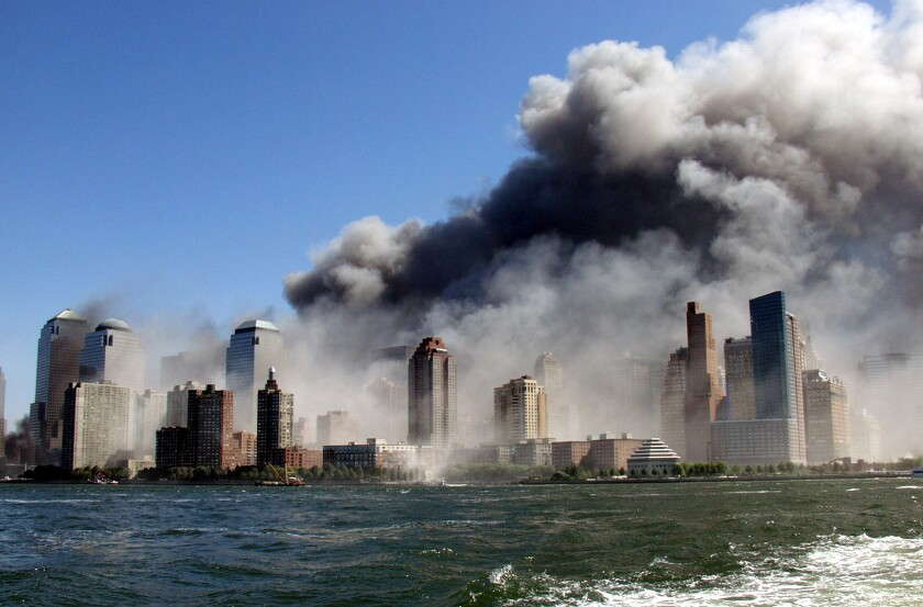 Smoke rises over the New York skyline in a photo taken from a tugboat.