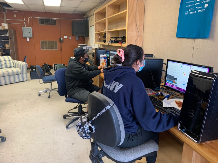 Cadets Leo Dinero and Hazel Galindo work their individual missions to support NJROTC's CyberPatriot team.