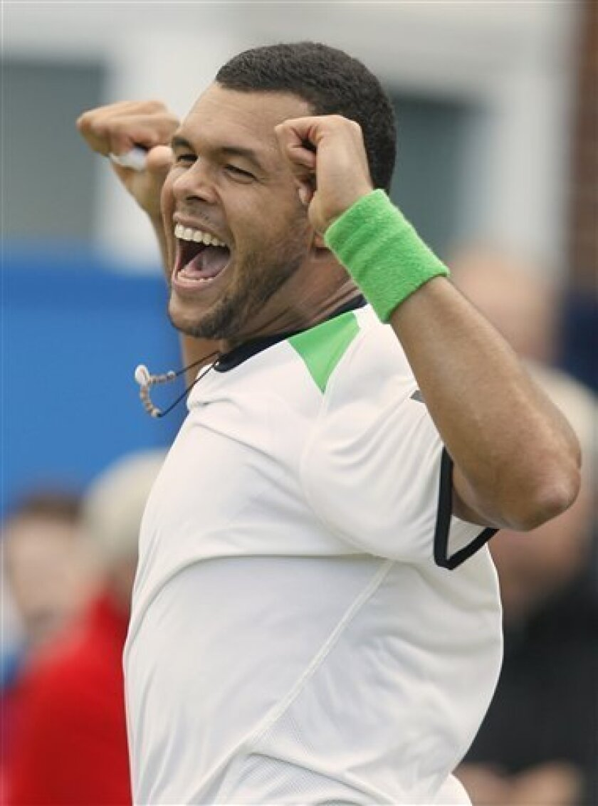 Jo-Wilfred Tsonga of France reacts after he defeated Rafael Nadal of Spain in his match at the Queens Club grass court tennis tournament in London, Friday, June 10, 2011. (AP Photo/Alastair Grant)