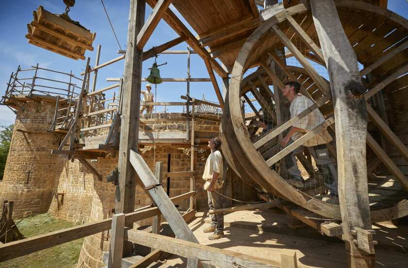 Masons drive the treadwheel crane at Guedelon medieval castle project, a back-to-the-future project re-creating a 13th century castle from scratch in the heart of Burgundy, central France.