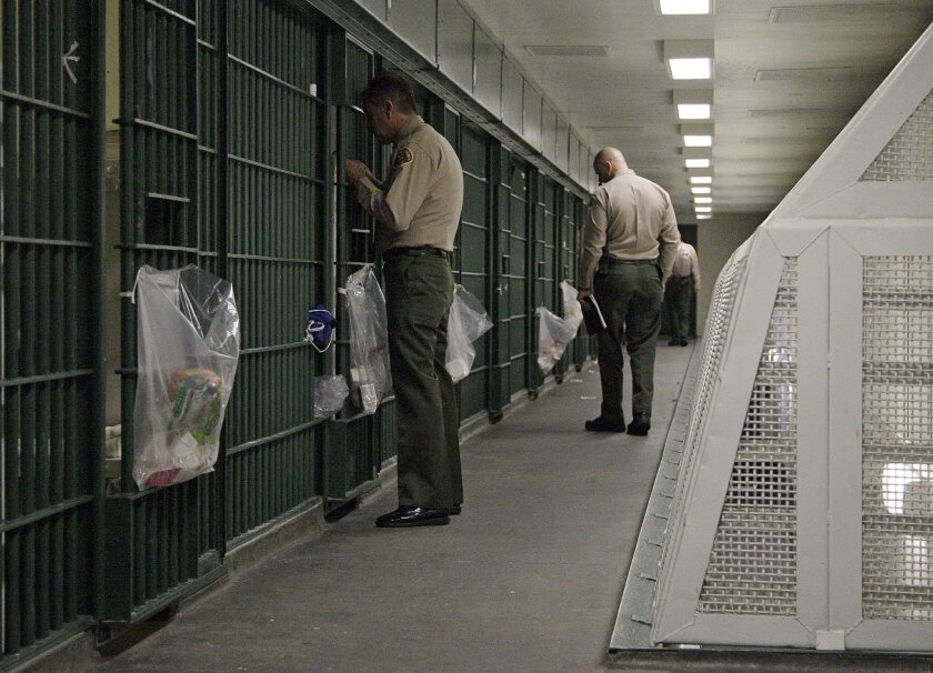 FILE - In this Oct. 3, 2012, file photo, Los Angeles County Sheriff's deputies inspect a cell block at the Men's Central Jail in downtown Los Angeles. The nation's largest sheriff's department agree
