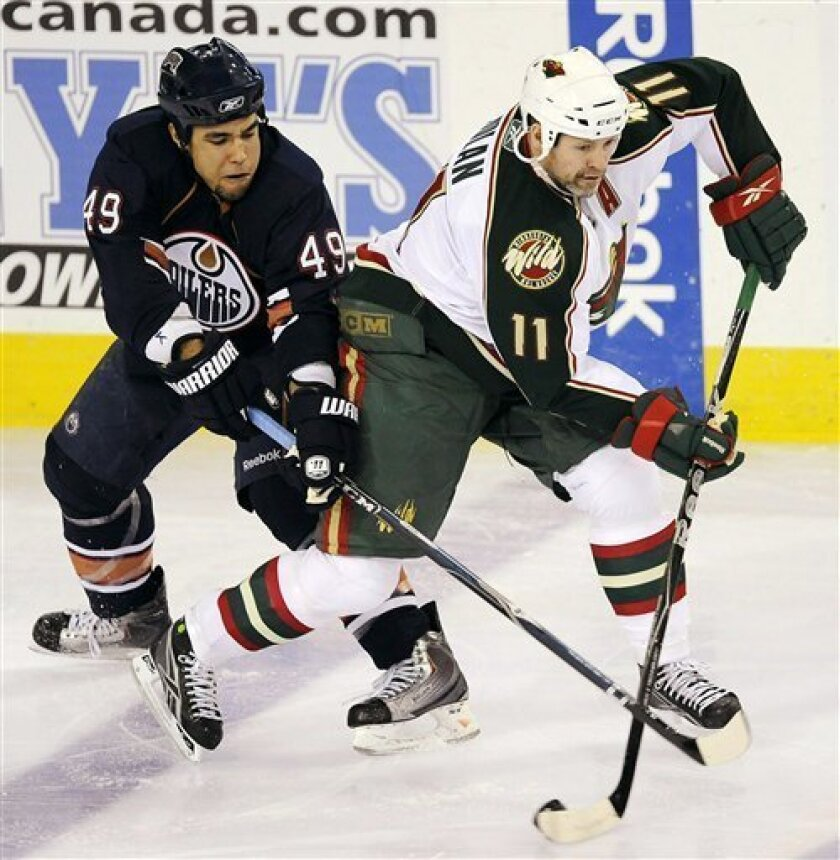 Edmonton Oilers' Theo Peckham (49) battles with Minnesota Wild's Owen Nolan (11) during the second period of an NHL hockey game in Edmonton, Alberta, on Friday, March 5, 2010. (AP Photo/The Canadian Press, John Ulan)