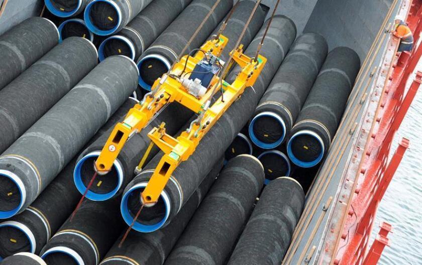 Fotografía de una grúa que carga tubos de acero a un buque de carga. EFE/Archivo