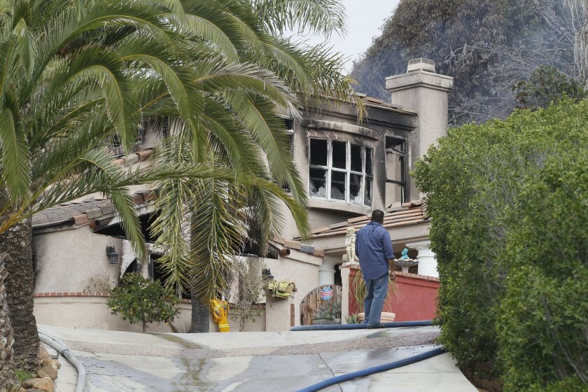 Sheriff Bomb Arson investigators combed through a hillside home in Encinitas that was heavily damaged in an early morning two-alarm fire that sent one man to the hospital.