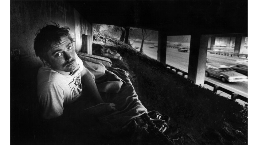 Nov. 8, 1982: Ton Kammer peers up from his bed, a mattress on dirt, beneath an overpass on the Hollywood Freeway. Behind Kammer are other mattresses with one sleeping neighbor.