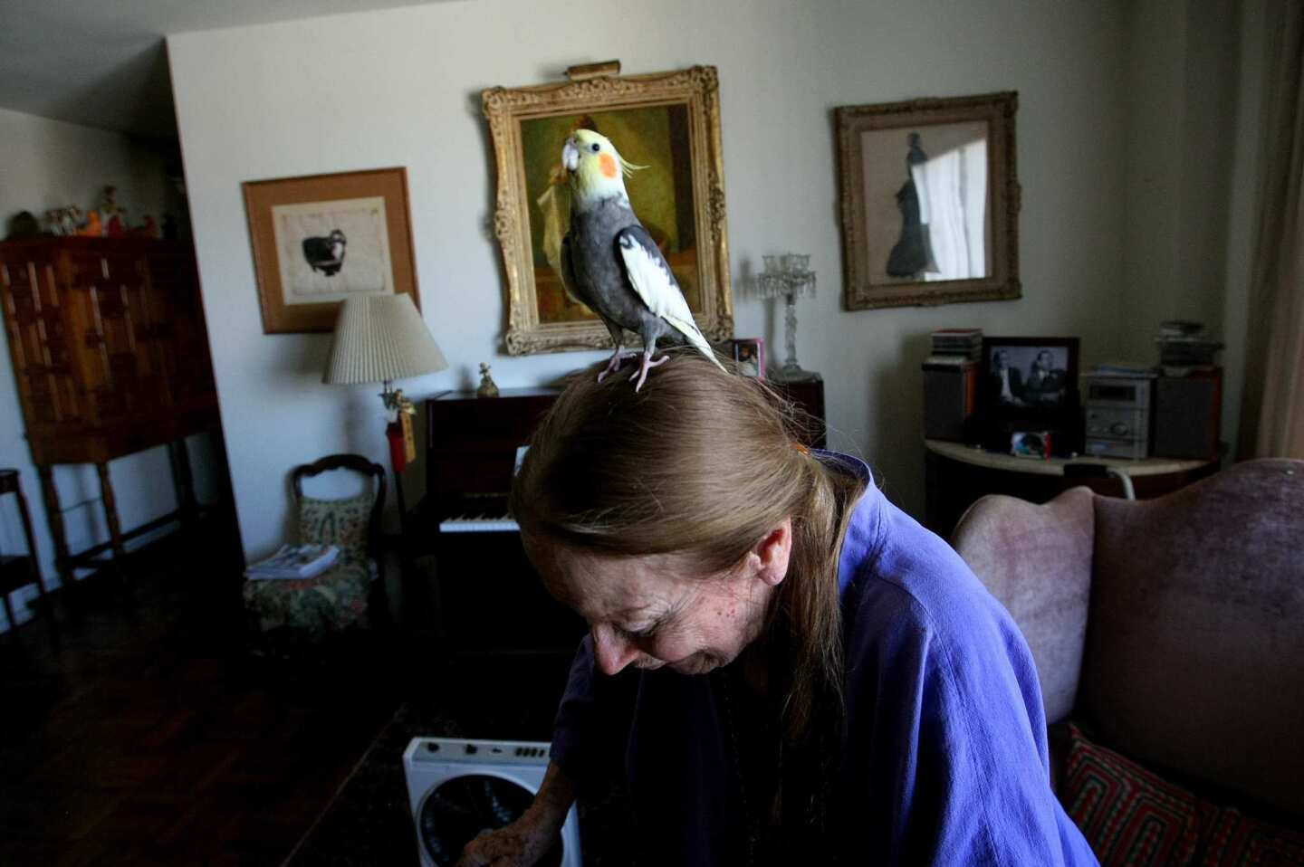 """Patricia Morison, 97, with cockatiel Cookie, has lived at Park La Brea for more than 50 years. Back when, """"It was more homogenous.... Most of the population was actors, actresses, artistic folks and businesspeople,"""" she says. """"There were never any children."""" About its evolution over the decades, she's philosophical: """"Life goes, life changes."""""""