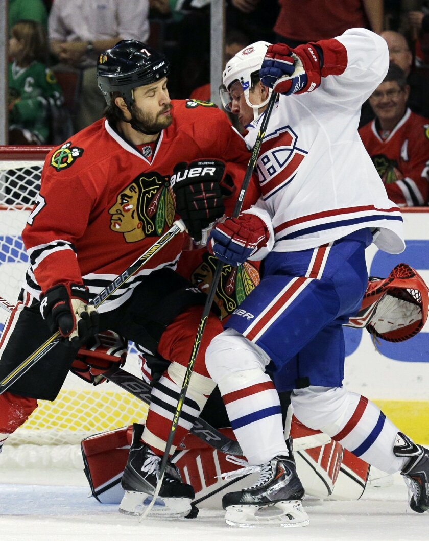 Chicago Blackhawks defenseman Brent Seabrook (7), left, and Montreal Canadiens left wing Christian Thomas (60) battle for the puck during the first period of a preseason NHL hockey game in Chicago, Wednesday, Oct. 1, 2014. (AP Photo/Nam Y. Huh)