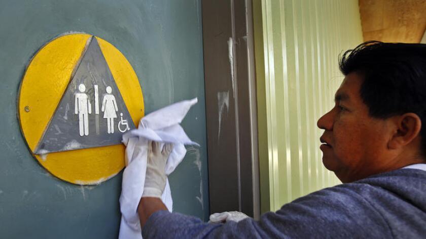 Edgar Lopez, un trabajador de mantenimiento de West Hollywood, limpia las puertas del baño en Plummer Park, el año pasado, meses antes de que se requieran instalaciones de género neutro en sitios y negocios de la ciudad.