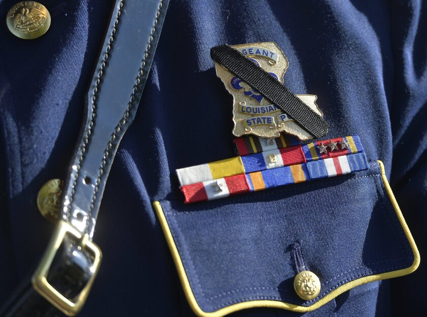 The badge of Louisiana State Police Officer Brett Travis is covered with a black band in remembrance of slain Kentucky State Police Trooper Joseph Cameron Ponder at the Severns Valley Baptist Church in Elizabethtown, Ky., Friday, Sept. 18, 2015. Ponder died Sunday night after being shot by a man he had stopped for speeding in western Kentucky. (AP Photo/Timothy D. Easley)