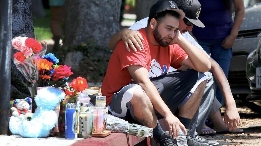 Familiares y amigos dan sus condolencias a Luis Anaya (izq.), cuya hija de cuatro años de edad recibió un disparo y murió, junto con la madre de la pequeña, en la intersección de 9th Street y Locust Avenue, en Long Beach, este sábado por la noche (Luis Sinco / Los Angeles Times).