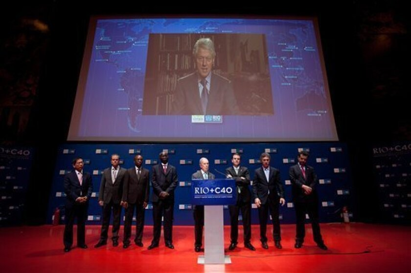 A live image of former President Bill Clinton is projected as he speaks with mayors, from left to right, Won Soon Park of Seoul, Ecktar Wuerzner of Heidelberg, Babatunde Fashola of Lagos, Franklyn Tau of Johannesburg, Michael Bloomberg of New York, Eduardo Paes of Rio de Janeiro, Eduardo Macri of B