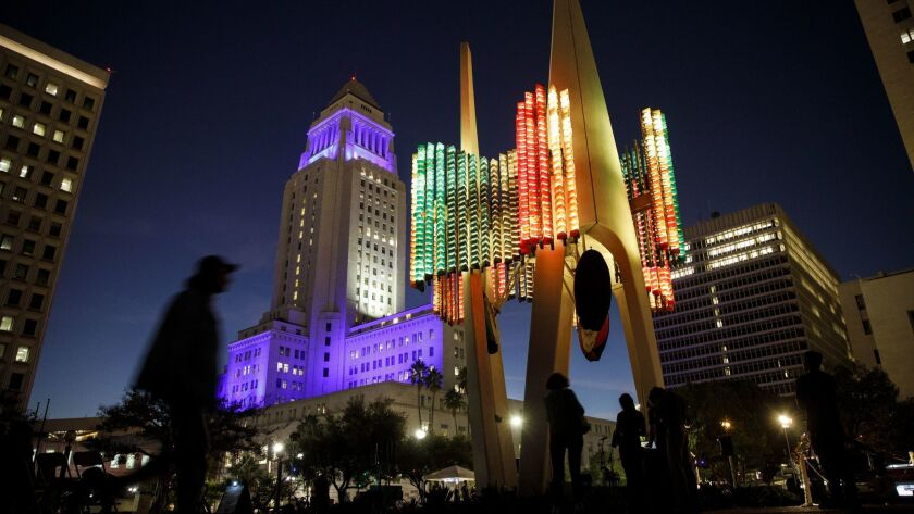The colored LED lights of the Triforium public artwork in downtown Los Angeles glow beneath City Hall, itself bathed in Dodgers blue, during a Triforium Friday performance on Oct, 26.