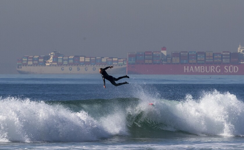 A surfer leaps off his board as about 20 container ships wait in line to be unloaded at the ports of L.A. and Long Beach.