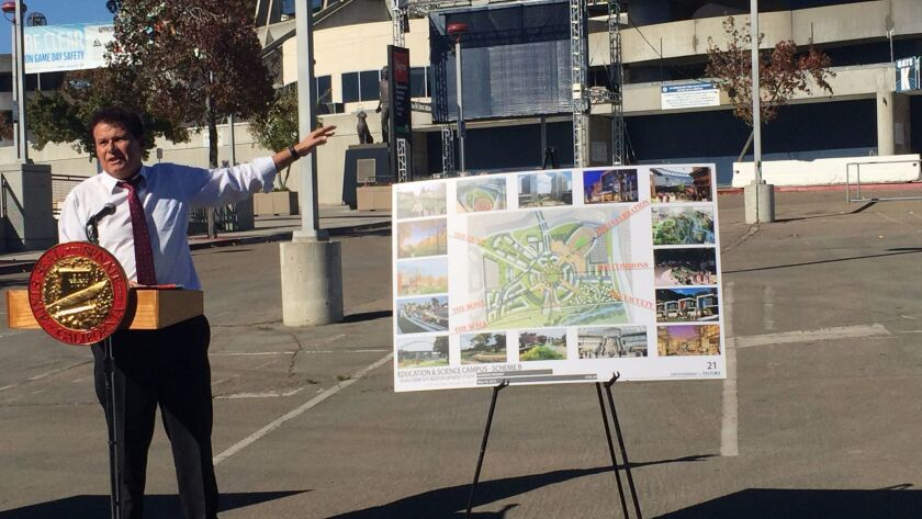 State Sen. Marty Block stands next to a rendering of a proposed San Diego State University satellite campus outside Qualcomm Stadium on Thursday.