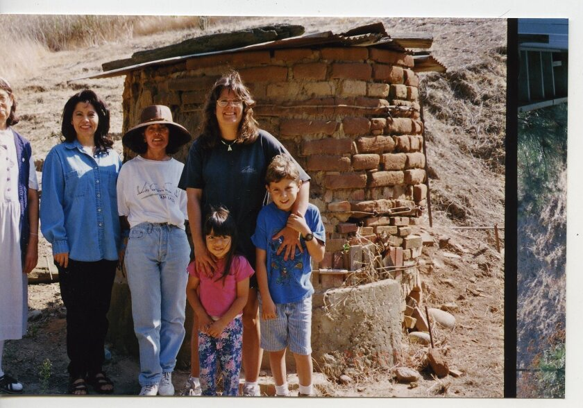 Sister Mary (cropped left) and the Rodriguez family with the kiln in the 1990s.