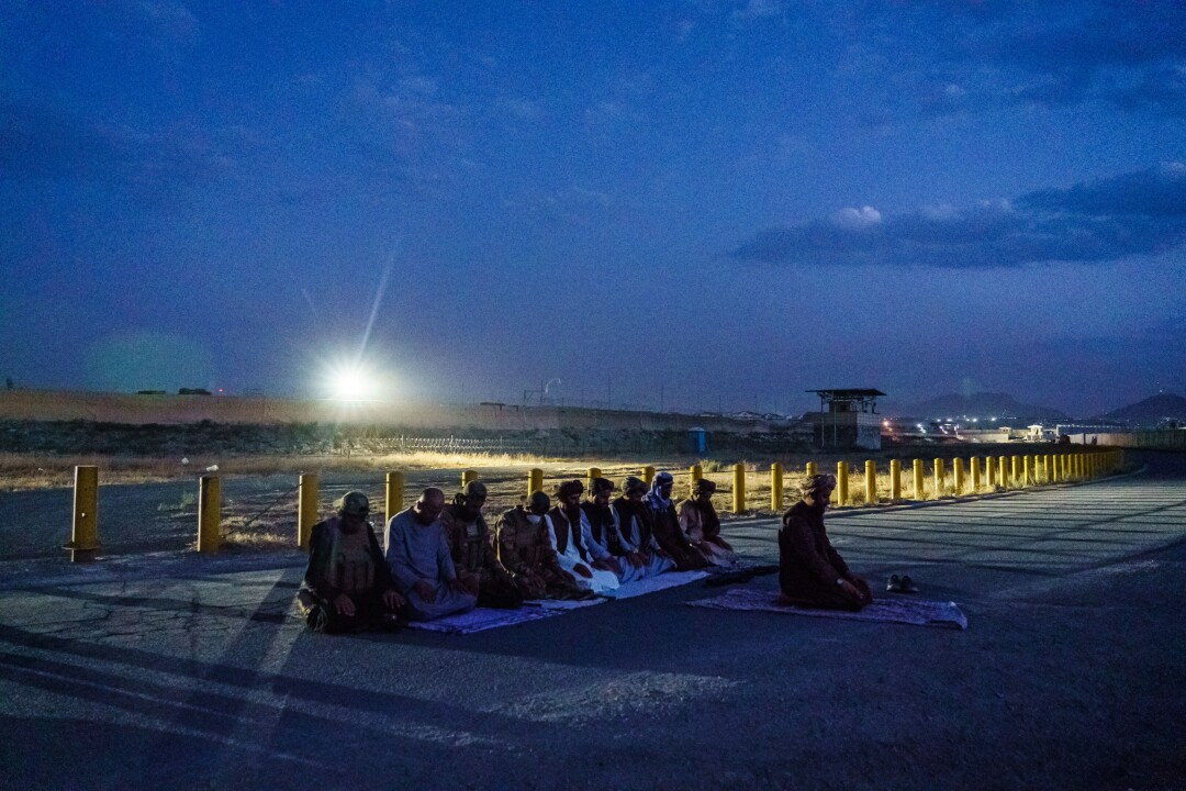 Taliban fighters kneel on the ground outside in the evening